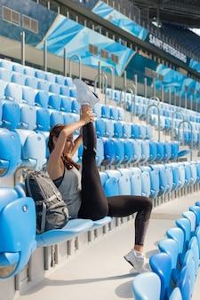 Jeune fille assise sur le siège du stade.