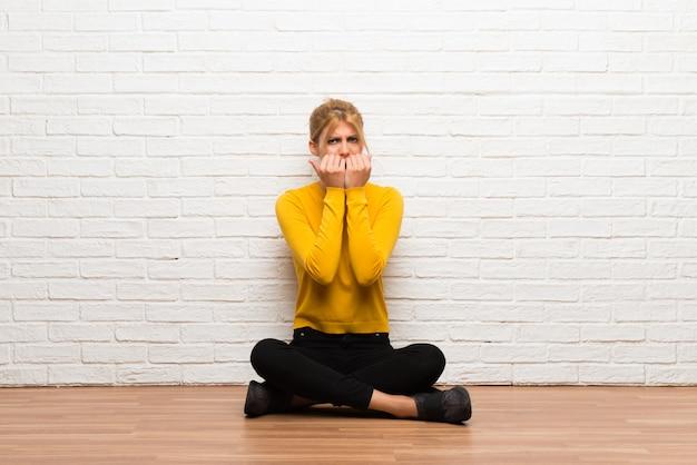 Une jeune fille assise sur le sol est un peu nerveuse et a peur de mettre ses mains à la bouche