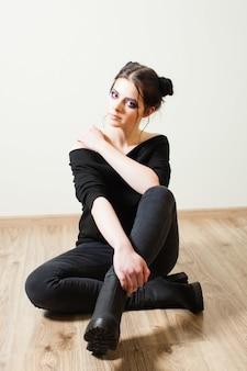 Jeune fille assise sur le sol en tailleur, se préparant à aller en boîte de nuit