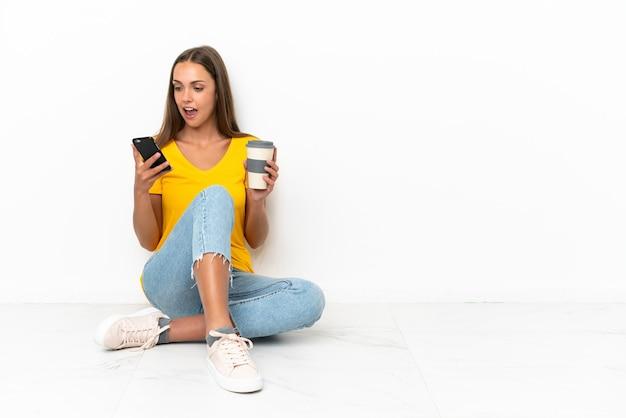 Jeune fille assise sur le sol tenant du café à emporter et un mobile
