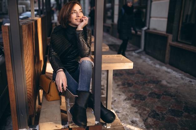 Jeune fille assise et souriant dans la rue sur un banc