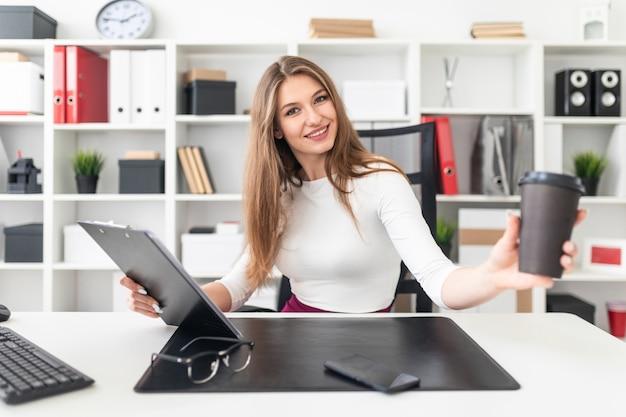 Une jeune fille assise à une table dans le bureau et tenant un verre de café et une tablette