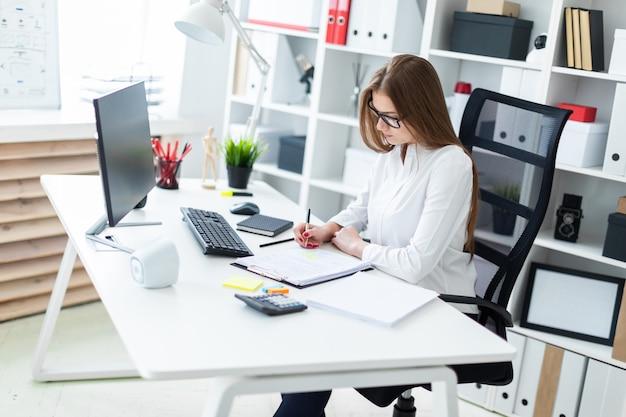 Une jeune fille assise à une table d'ordinateur et remplit les documents.