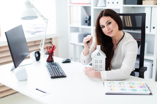Une jeune fille assise à table, tenant les clés et l'agencement de la maison.