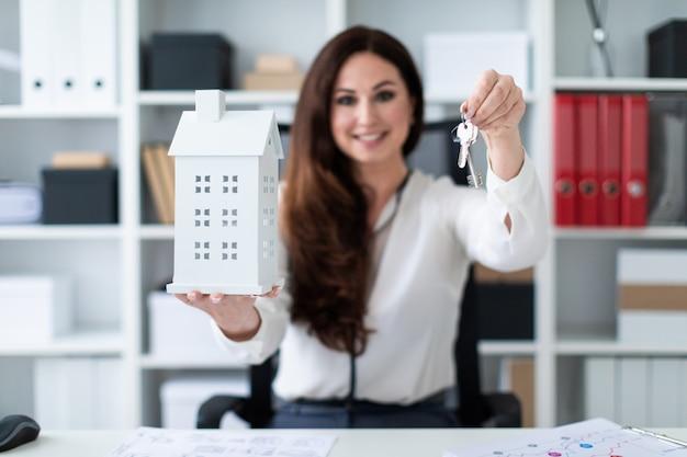 Une jeune fille assise à une table et tenant une maison et des clés.