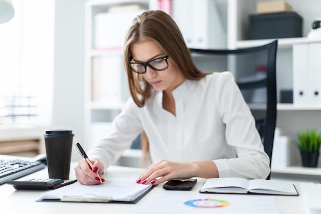 Jeune fille assise à la table et travaillant avec des documents et une calculatrice