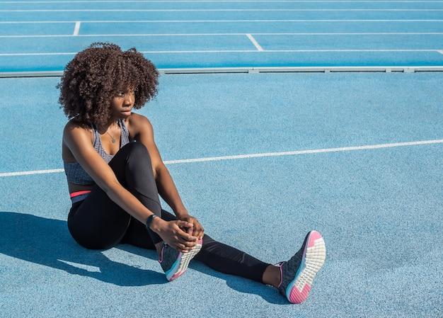 Jeune fille athlète noire aux cheveux afro s'étirant assise en tenue de sport noire et haut gris avec piste de course bleue en arrière-plan