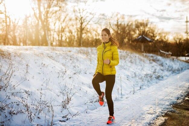 Jeune fille athlétique active jogging en vêtements de sport d'hiver sur la route d'hiver enneigée avec des écouteurs dans la matinée ensoleillée.