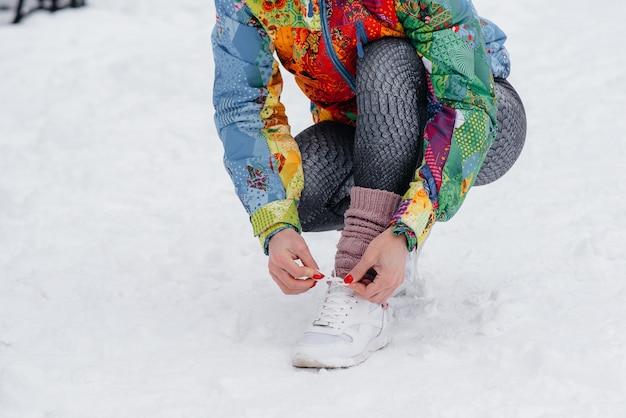 Jeune fille athlétique attache ses chaussures un jour givré et neigeux. fitness, course à pied