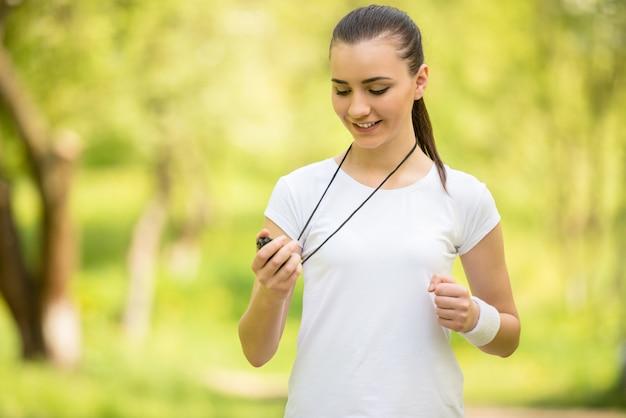 Jeune fille athlétique attrayante tenant le chronomètre.