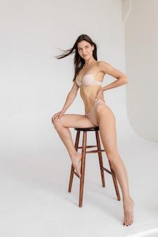 Une jeune fille athlétique et en forme en sous-vêtements blancs mur isolé le concept de publicité pour les sous-vêtements de fitness