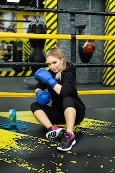 Une jeune fille athlétique en survêtement noir est assise sur le ring et se repose après une séance d'entraînement.
