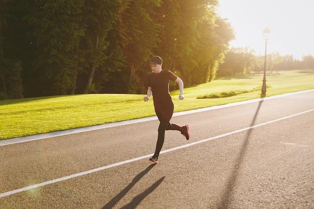 Jeune fille athlétique en uniforme noir et entraînement à la casquette, faisant des exercices sportifs, courant, regardant droit sur le chemin dans le parc de la ville à l'extérieur par une journée ensoleillée de printemps ou d'été. remise en forme, concept de mode de vie sain.
