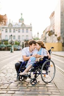 Jeune fille atteinte de maladie sur un fauteuil roulant et son bel homme