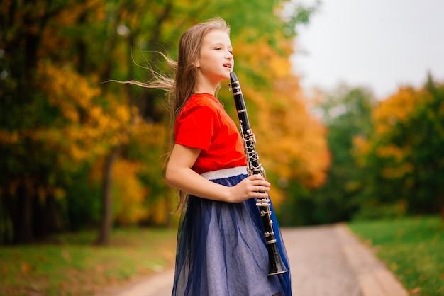 Jeune fille attirante jouant de la clarinette, ébène dans le parc d'automne