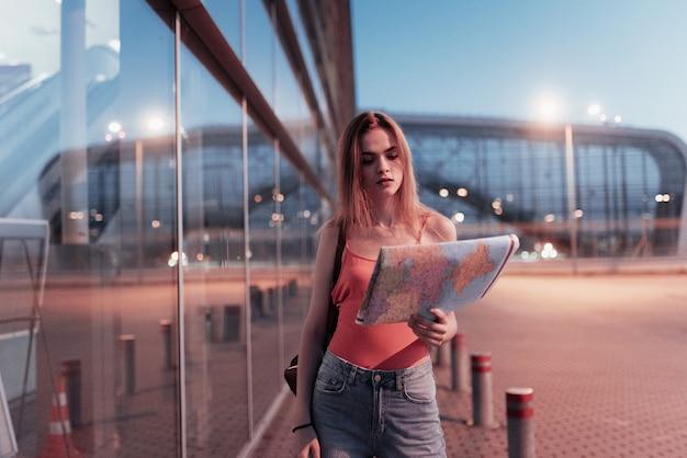 Jeune fille attirante regardant la carte dans sa main tout en marchant près du bâtiment d'affaires