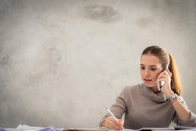 Jeune fille attrayante parlant sur le téléphone portable et souriante tout en restant seule dans un café pendant le temps libre et en travaillant sur une tablette informatique. heureuse femme qui se repose dans un café. mode de vie