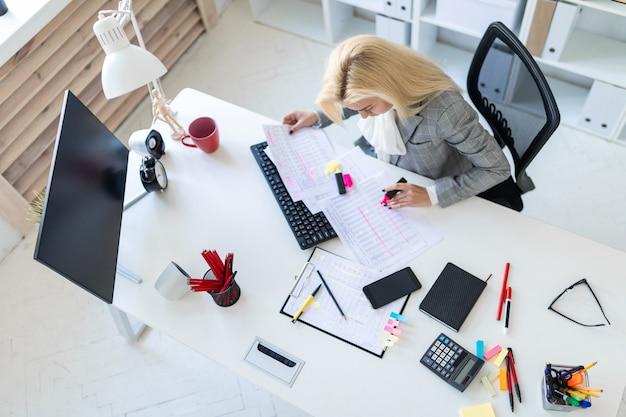 Jeune fille au bureau avec un marqueur et des documents
