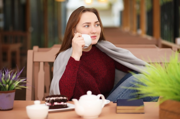 Jeune fille au café s'assoit et boit du thé avec un dessert