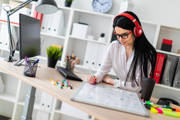 Une jeune fille au casque se tient près de la table et dessine un marqueur sur un tableau magnétique.