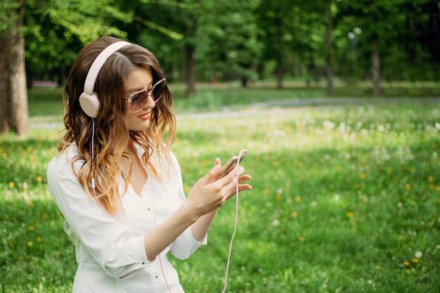 Jeune fille au casque et avec un smartphone apprend