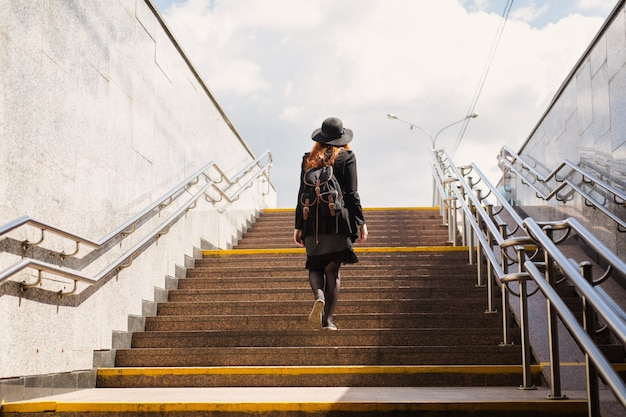 Jeune fille au chapeau aux cheveux rouges s'élève du passage souterrain. une femme sort du métro.