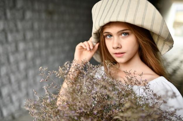 La jeune fille au chapeau avec les fleurs.