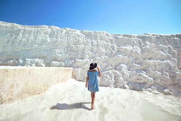 Jeune fille au chapeau à la recherche sur les piscines et terrasses en travertin à pamukkale. château de coton dans le sud-ouest de la turquie