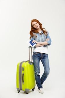 Jeune fille au gingembre, debout avec valise et tenant un passeport avec des billets.