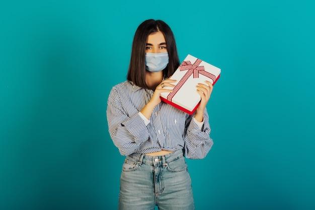 Jeune fille au masque médical tient une boîte cadeau blanche avec un arc rouge, isolé sur une surface bleue.