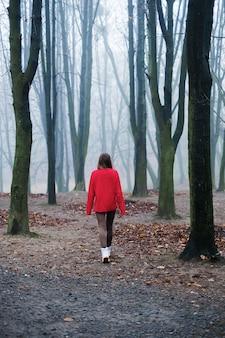 La jeune fille au pull rouge marche seule dans la froide forêt brumeuse