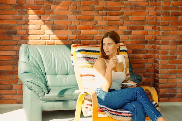 Jeune fille au regard pensif profite d'une belle journée assise dans un fauteuil à bascule avec une tasse de son café.