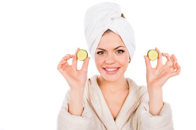 Jeune fille au spa avec des tranches de concombre dans ses mains