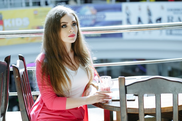 Jeune fille au visage grave assis à une table de restaurant