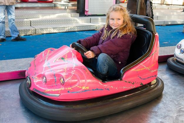 Jeune fille au volant d'une voiture tamponneuse