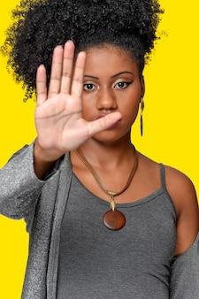 Jeune fille aux cheveux afrostyle portant un masque de protection contre les coronavirus isolé covid19 sur le dos gris