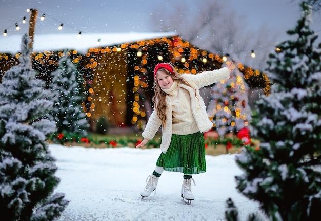 Jeune fille aux cheveux assez longs patinant à la patinoire ouverte. fond de noël.