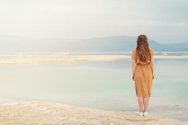 Jeune fille aux cheveux blonds brillants va au bord de la mer