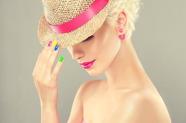 Jeune fille aux cheveux blonds élégante, vêtue d'un chapeau de paille avec un ruban rose, fait la démonstration d'un maquillage brillant à la mode et d'un vernis à ongles multicolore sur ses ongles. mode, manucure et cosmétique.