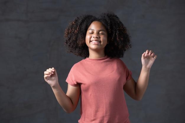 Jeune fille aux cheveux bouclés afro-américains dansant