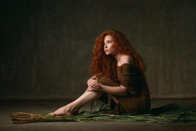 Jeune fille aux cheveux bouclés rouges est assis sur une canne sèche dans une robe de couleur kaki