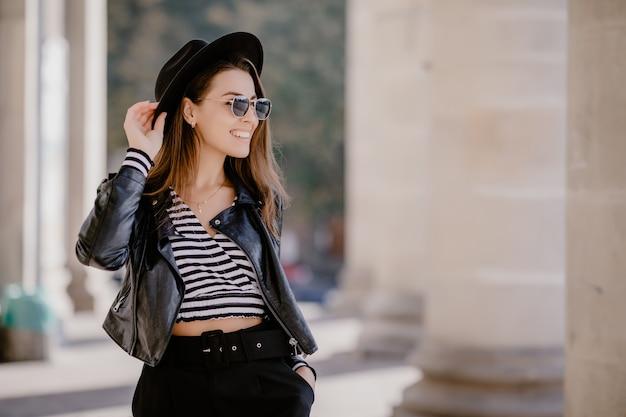 Jeune fille aux cheveux bruns français dans une veste en cuir, chapeau noir sur la promenade de la ville
