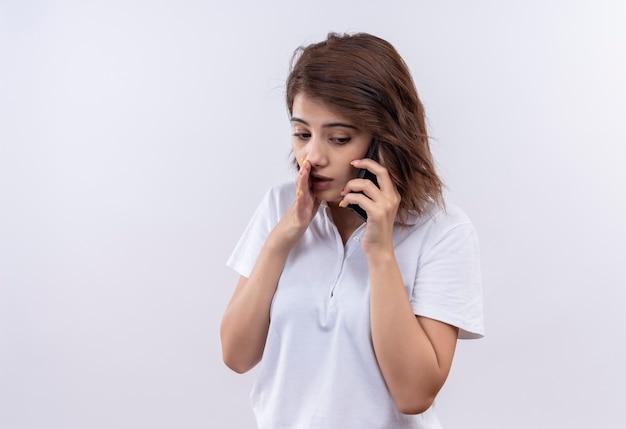 Jeune fille aux cheveux courts portant un polo blanc chuchotant en disant un secret tout en parlant au téléphone mobile