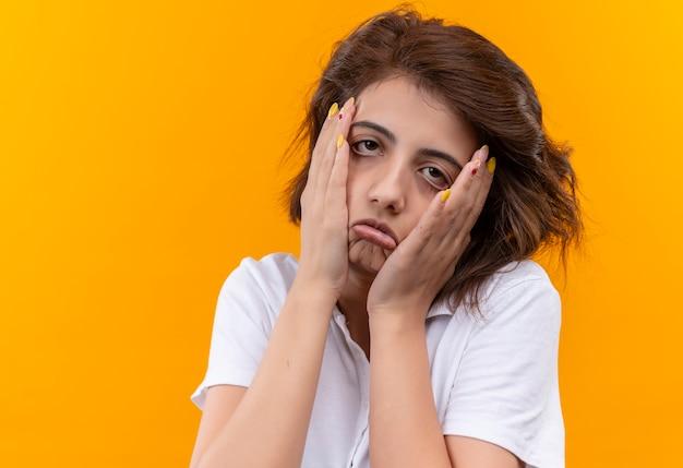Jeune fille aux cheveux courts portant un polo blanc à la fatigue et la peine de toucher le visage avec les mains