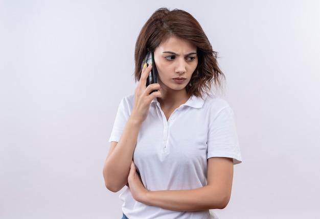Jeune fille aux cheveux courts portant un polo blanc parlant au téléphone mobile avec froncement de sourcils