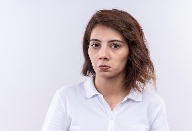 Jeune fille aux cheveux courts portant un polo blanc regardant la caméra en fronçant les sourcils et mécontent