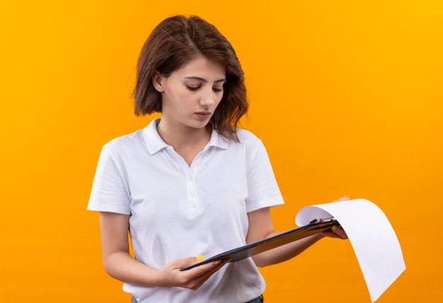 Jeune fille aux cheveux courts portant un polo tenant le presse-papiers avec des pages blanches en le regardant avec un visage sérieux