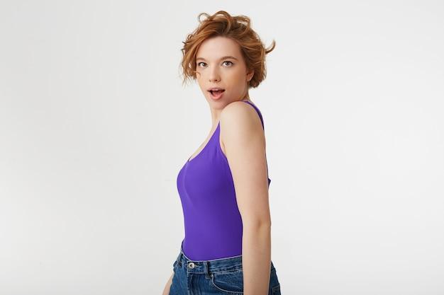 Jeune fille aux cheveux courts séduisante surprise, vêtue d'un maillot violet, posant de profil, regardant avec la bouche et les yeux grands ouverts, elle a entendu la nouvelle. isolé sur un mur blanc.