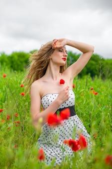 Une jeune fille aux cheveux longs apprécie les couleurs de la nature sur un champ de pavot en fleurs par une chaude journée d'été.