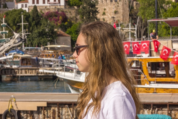 Jeune fille aux cheveux longs est assis sur la jetée dans le port de plaisance et regarde la mer bleue